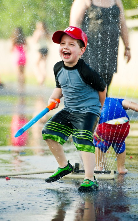 Camden Lurie, 4, laughs as he plays in a sprinkler during the Centerpoint Church Kids Life water battles at the church.