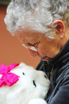 A Carlyle Place resident Jeanette Tally, 85, holds Lucy, a robotic baby harp seal, during a group session before lunch. Each resident in the session got a few minutes with the doll. The doll reacts to touching and speaking to it by moving, closing its eyes and making sounds.