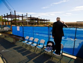 Mercer University President Bill Underwood stands in a chair to get a look over the fence at the Spearman C. Godsey Science Center under construction. The building will have four stories and a basement when completed in December 2017. It will have more than 30 laboratories. Underwood was on hand for a beam signing ceremony where students were invited to sign their names on the last beam to be installed in the building.