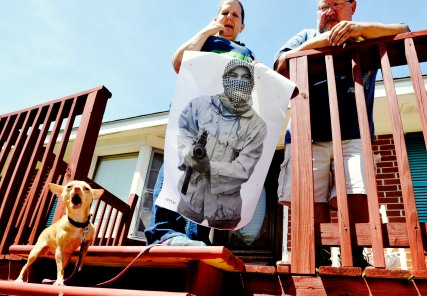 Honey, a 1-year-old teacup Chihuahua, barks as Larry and Carol Womack pose on the front porch of their home. Honey attacked an armed robber as he tried to force the Womacks into their home. Carol is holding a target from a recent trip to the shooting range.