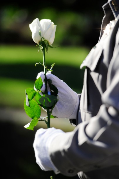 A Bibb County Deputy holds a white rose before placing it at the Macon Police monument at the annual Peace Officers Memorial Day observance in the Mulberry Street Park. The ceremony recalls the ultimate sacrifices of Macon police officers, Bibb County sheriff's deputies and Macon-Bibb County firefighters who died while on duty.