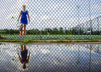 "Grace Howell is reflected in a rain puddle as she chases down an out-of-bounds tennis ball during at Middle Georgia State College. She was at Covenant Academy tennis practice preparing for the start of the GICAA tennis regional at John Drew Tennis Center Wednesday. Coach Gwen Wood said, ""The weather is good for tennis, except for the humidity."""