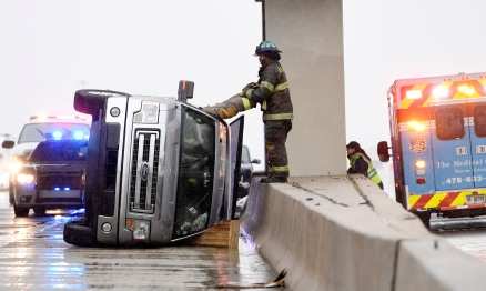 A Macon-Bibb County firefighter holds onto the legs of one of his fellow firefighters that is lowered into the passenger compartment of a overturned vehicle. The driver of the truck, Steven Zimvler, said he was driving on I-75 south just before the Hartley Bridge Road when a car hydroplaned into a transfer truck and then back into his lane. The car struck his truck in the right rear as he tried to avoid it. Zimvler's truck turned over in the road and came to rest in the breakdown lane under the Hartley Bridge Road bridge.