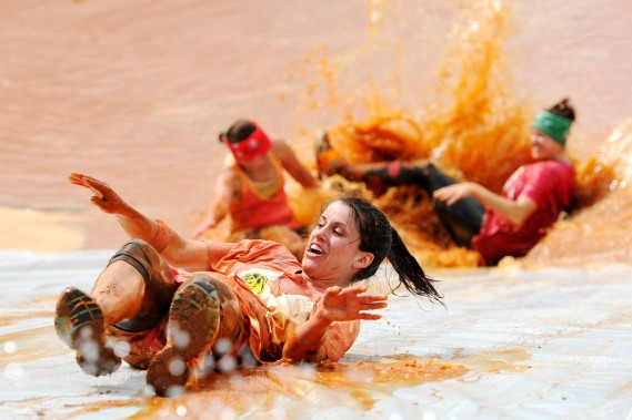 A racer slides backwards down a slide and into a shallow mud pit during the Macon Mud Run at Hephzibah Children's Home Saturday morning. The 7K and 5K course includes obstacles, pond crossings, hills, slides, tunnel crawls, and mud pits.