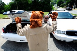 McGruff the Crime Dog puts his paws in the air as he gets help into the costume in the Centenary Church parking lot. Bibb County Sheriff's Office Outreach division deputies Santel Smith and Emmett Bivins were getting ready to make crime prevention appearance for senior citizens event in Tattnall Square Park.