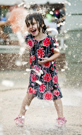 Madeline Thomas, 3, plays in the Cherry Street fountain at the 100th year Nu-Way Weiners and Terminal Station celebration.