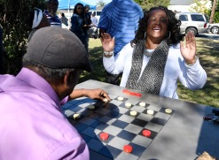 "Bibb County Commissioner Elaine Lucas reacts as she is triple jumped during a game of pool checkers. ""I gave her one."" (a king) said her opponent, checkers champion, Alfred ""East Point"" Barnett after the match at the new Chess/Checker/Connect 4 Park on Lynmore Avenue. The new park is the latest project by the South Macon Arts Revitalization Technology organization. SMART received a grant from the American Association of Retired Persons to build the playing tables and two large Connect 4 games in the park. Lucas said about the game, ""I know when I've met my match."""