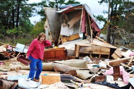 Sue Freeman looks through her destroyed mobile home for pieces of a child's roll top desk that was stored in it. Twiggs County Sheriff Chief Deputy Billy Boney said he thought it was thinks a tornado that briefly touched down on the property.