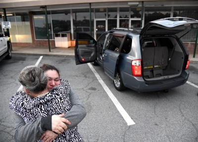 Sandra Torres, right, hugs The Mentors Project's June O'Neal after she was presented with a Kia van. Interstate Auto Sales presented Torres with the van and a check for $200. Torres has been walking miles back and forth to work and needed a vehicle.