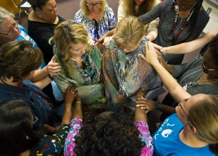 Wendy Wood and Shannon Grieshop stand in the middle of a prayer circle Wednesday. The Hilltop Elementary School paraprofessional and teacher, surrounded by their coworkers, have hands laid on them as they are prayed for at an after school meeting of the Teachers Living for Christ. Grieshop will be receiving a kidney from Wood at Emory University.