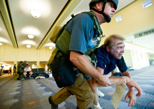 A SWAT Team member helps a victim leave the Middle Georgia Regional Airport terminal. The airport was the scene for disaster scenario training that included active shooters inside the airport terminal, reports of an IED and lockdown of the airport and a hostage situation in a nearby building.
