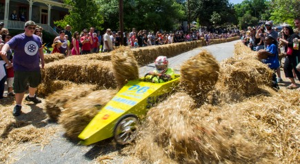 Hay bales fly as Carlos Aeschlimann crashes through the end of the track at the Magnolia Soap Box Derby.