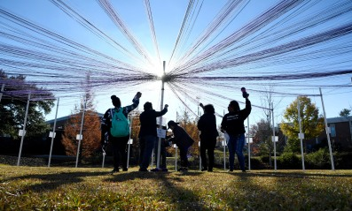 Middle Georgia State University students string yarn from post to post at an interactive public art installation on campus.