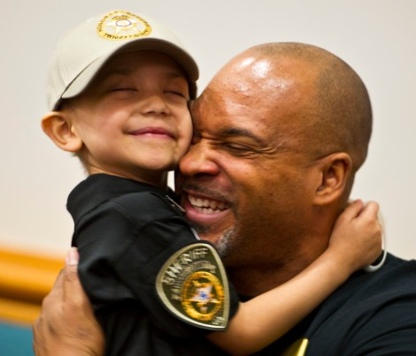 Karma Lilly Little, 6, hugs Jamie Paulk, her Jeffersonville Elementary School principal, after Sheriff Darren Mitchum made her an honorary deputy sheriff. Karma Lilly is battling stage four Neuroblastoma cancer and has dreamed of being a law enforcement officer since she befriended police officers in New York City visiting her in the hospital where she is undergoing a medical trial.
