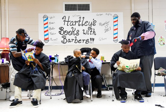 "Boys sit and read as they get their hair cut at Hartley Elementary School. Boys got free haircuts during the ""Books with Barbers"" event at the school. A partnership between several local barbers and the school's Family Engagement program made the haircuts possible. The boys read books while the barbers cut their hair."