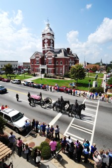 Citizens line the streets around the courthouse in Forsyth as they pay their respects to Monroe County deputy William Norris' funeral procession. Norris and Jeff Wilson were shot while answering a call about an attempted suicide near Bolingbroke. Christopher Keith Calmer, 46, is charged with murder in the death of Norris and faces other charges in the incident. Norris is the first Monroe deputy killed in the line of duty in the agency's history, according to the sheriff's office.
