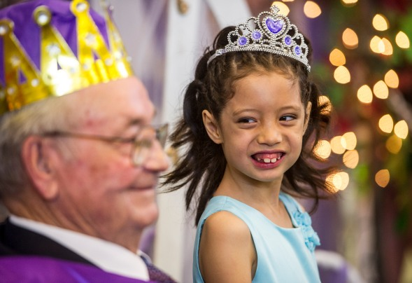 Arthur Elementary School first grader Ariel Her smiles at the school's namesake Matt Arthur, Prince Charming, while having her photo made during the school's Cinderella Ball.