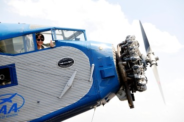 Jake Gallegos, 13, gives the thumbs up to his father, Gerald, as he sits in the co-pilot seat of the 1929 Ford Tri-Motor at the Perry Airport. He and his father took a flight in the Friday.