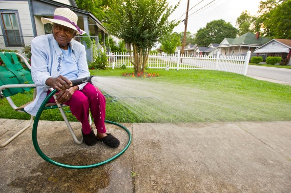 "Mary Jackson, 88, waters the grass in her front yard at her home on Montpelier Avenue. Of her yard she said, ""It ain't pretty yet. You wait until the flowers bloom."""