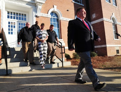 "Telfair County Sheriff Chris Steverson walks in front of Ronnie Adrian ""Jay"" Towns as Towns is lead from the courthouse to a waiting sheriff's cruiser. Towns has been charged with murder and armed robbery in the deaths of Bud and June Runion, according to Telfair County Sheriff Steverson."